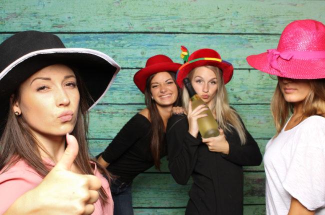 4 Mädchen mit Damenhüten und Sekt vor einer Fotobox - Mädchen zeigen Daumen hoch