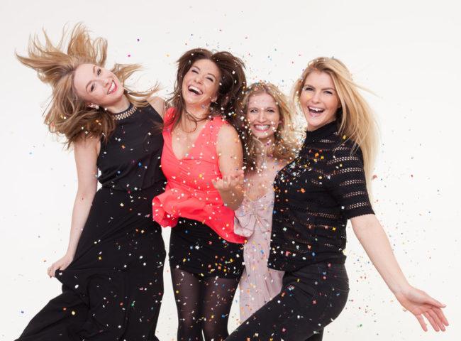 Junge Frauen feiern ausgelassen vor Fotobox